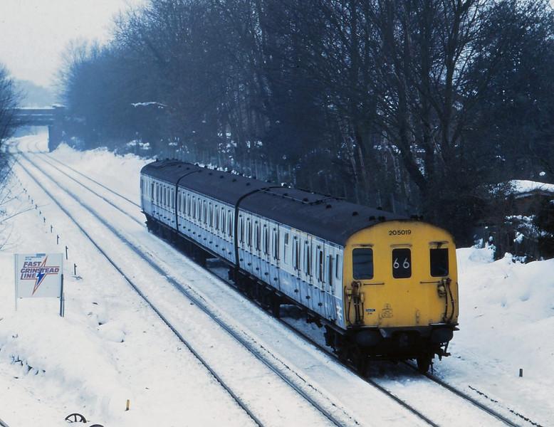 Class 205 DEMU 205019 runs through a snowy landscape around Hurst Green on its way back into London